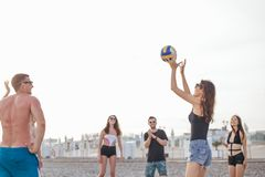 People group have fun and play beach volleyball at summer day. Young people group have fun and play beach volleyball at summer day royalty free stock images