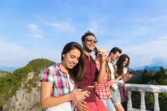 Young People Group In Mountain Using Cell Smart Phone Chatting Online Friends Asian Holiday Summer. Vacation Travel stock image