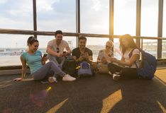 Young People Group Sitting On Floor Airport Lounge Waiting Departure Use Cell Smart Phone Chatting Mix Race Friends. Happy Smile Flight Delay stock photo
