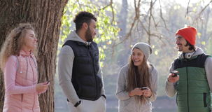 Young People Group Speak Hold Smart Phone Outdoor Sunrise, Two Couple Communication Morning Autumn Park Near Tree stock video footage