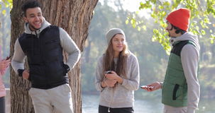 Young People Group Speak Hold Smart Phone Outdoor Sunrise, Two Couple Communication Morning Autumn Park Near Tree stock footage