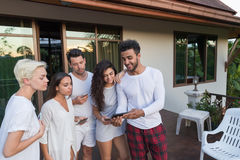Young People Group On Terrace Tropical Hotel, Friends Using Cell Smart Phone Tropic Holiday Vacation Royalty Free Stock Image