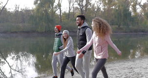 Young People Group Walking Countryside Two Couple Outdoor Near River Shore, Friends Speaking Morning Autumn Park. Natural Sun Lights Slow Motion 60 Fps stock footage