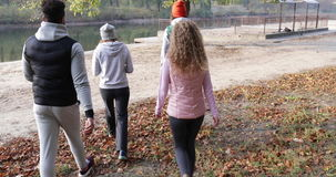 Young People Group Walking Countryside Two Couple Outdoor Near River Shore, Friends Speaking Morning Autumn Park. Natural Sun Lights Slow Motion 60 Fps stock video footage
