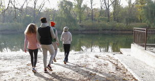 Young People Group Walking Two Couple Outdoor Near River Shore, Friends Speaking Morning Autumn Park. Natural Sun Lights Slow Motion 60 Fps stock video footage