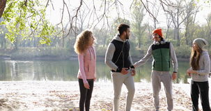 Young People Group Walking Two Couple Outdoor Near River Shore, Friends Speaking Morning Autumn Park. Natural Sun Lights Slow Motion 60 Fps stock video