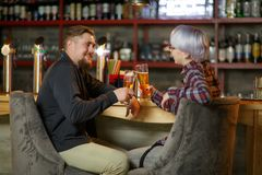 Guy and girl, spend free time in bar, communicate and drink beer. Indoors. stock image