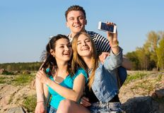 Young people - a guy and two girls - laugh and do selfie in the. Young people - a guy and two girls, teens - laugh and do selfie in the open air Royalty Free Stock Images