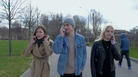 Young people, a guy and two girls are walking in the park and talking on the phones. Good sunny day. stock video