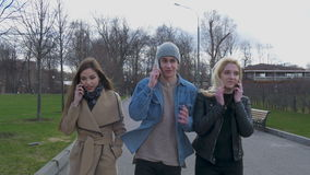 Young people, a guy and two girls are walking in the park and talking on the phones. Good sunny day. stock footage