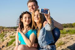 Young people - a guy and two women - laugh and do selfie in outd. Young people - a guy and two women, brunette and blonde - laugh and do selfie in the open air Stock Photo