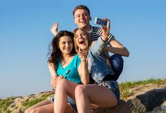 Young people - a guy and two women - laugh and do selfie in the. Young people - a guy and two women, brunette and blonde - laugh and do selfie in the open air Royalty Free Stock Photo