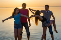 Young people, guys and girls, students are dancing on the beach. At sunset background Stock Photography