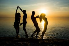 Young people, guys and girls, students are dancing on the beach. At sunset background, silhouettes Royalty Free Stock Images