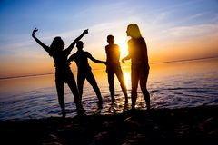 Young people, guys and girls, students are dancing on the beach. At sunset background, silhouettes Royalty Free Stock Image