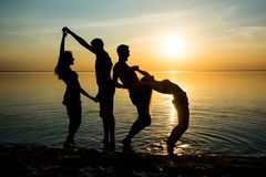 Young people, guys and girls, students are dancing on the beach. At sunset background, silhouettes Stock Images