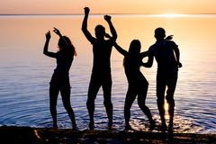 Young people, guys and girls, students are dancing on the beach. At sunset background, silhouettes Royalty Free Stock Photography