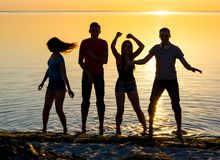Young people, guys and girls, students are dancing on the beach. At sunset background, silhouettes Royalty Free Stock Photo