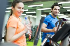 Young people in the gym. Young people training on a cross trainer Royalty Free Stock Photo
