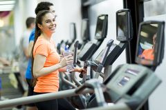 Young people in the gym. Young people training on a cross trainer Royalty Free Stock Photography