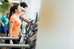 Young people in the gym. Young people training on a cross trainer Stock Photos