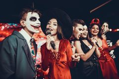 Young People in Halloween Costumes Singing Karaoke stock photo