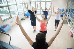 Young people with hands in the air in a yoga class Stock Photo