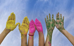 Young people hands covered in Holi Colors. Hands / Palms of young people covered in pink, yellow, green Holi festival colors royalty free stock photo