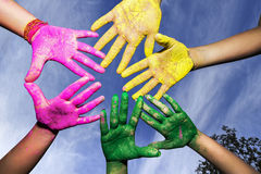 Young people hands covered in Holi Colors under blue sky. Hands / Palms of young people covered in pink, yellow, green Holi festival colors under blue sky Stock Photos