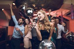 Young people have fun in a nightclub and sing in karaoke. In the foreground there is a woman in a black dress. Young people have fun in a nightclub and sing in Royalty Free Stock Photo