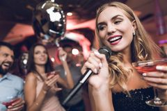 Young people have fun in a nightclub and sing in karaoke. In the foreground there is a woman in a black dress. Royalty Free Stock Photos