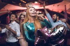 Young people have fun in a nightclub and sing in karaoke. In the foreground, a woman in a green dress. Stock Photo