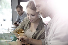 Young people having a break in a snack bar sharing information on a smartphone Royalty Free Stock Image
