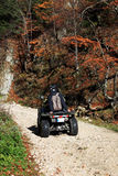 Young people having fun with ATV motorcycle. This image presents two young people having fun with an ATV motorcycle on a mountain road Stock Photography
