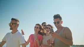 Young People Having Fun on the Beach Using Phones. Medium shot. Soft Focus Royalty Free Stock Photography