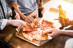 Young people having fun with beer and pizza. Close-up partial view of young people having fun with  beer and pizza Stock Image