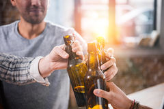 Young people having fun and clinking beer bottles. Close-up view of young people having fun and clinking beer bottles Stock Photo