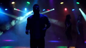 A modern young guy dances in the dark in nightclub. Young people are having fun in the club, friends dancing at a party. Silhouette of a stylish guy who dances stock video
