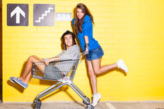 Young people having fun in front of yellow brick wall. Beautiful long haired girl in jeans mini skirt rides a boy in hat on shopping trolley in front of yellow Stock Photo