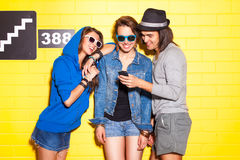 Young people having fun in front of yellow brick wall Stock Photography