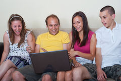 Young people having fun with laptop. Group of four young people watching something on laptop at home, reacting surprised and laughing Royalty Free Stock Images