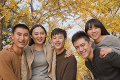 Young people having fun and playing piggyback in the park in autumn Royalty Free Stock Photos