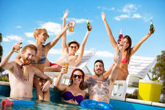 Young people having fun in pool with drinks in arms Royalty Free Stock Photos