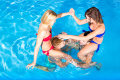 Young people having fun in the pool Stock Image