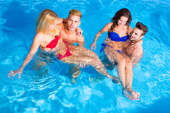 Young people having fun in the pool Stock Images