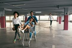 Young People Having Fun, Racing On Shopping Trolley At Parking stock images