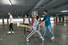 Young People Having Fun, Racing On Shopping Trolley At Parking royalty free stock image