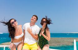 Young people having fun and standing on the yacht at a sunny sum Royalty Free Stock Photography