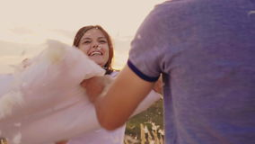 Young people having fun. A woman is beating her pillow with a friend, feathers are flying. Fight against the pillows stock video