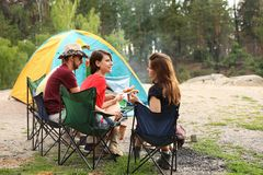 Young people having lunch with sausages. Near camping tent outdoors stock photo
